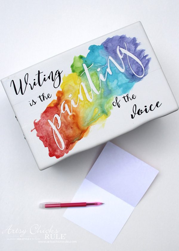 white box with rainbow and writing quote