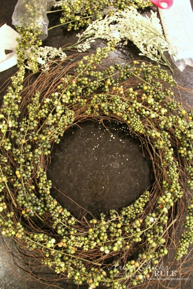 Adding the green berry sprigs to the wreath