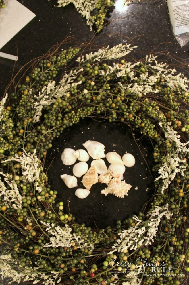 Adding the white sprigs to the wreath