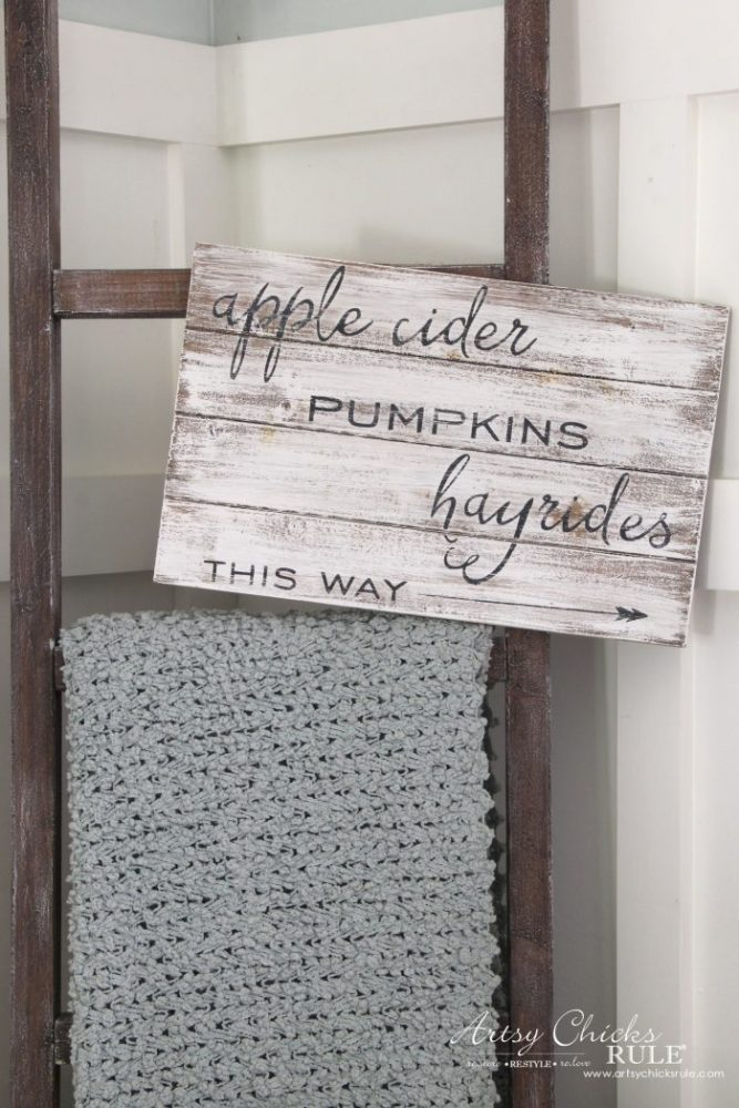 whitewashed sign hanging on ladder with apple cider saying