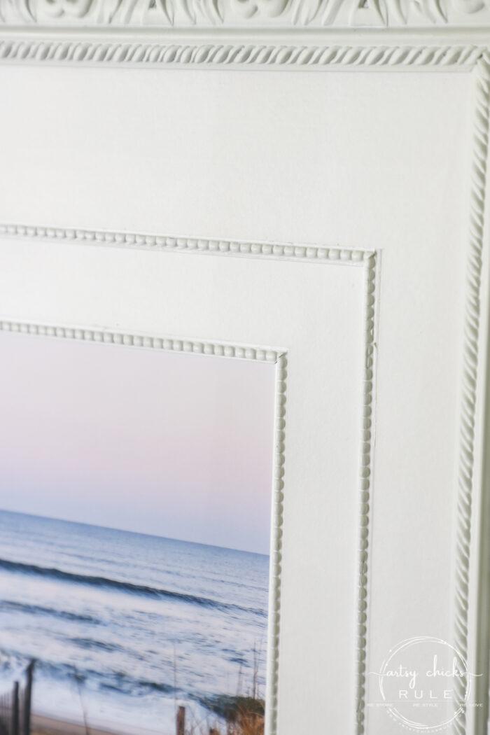 This beach scene wall art cost me SIX dollars! Yep! An old thrift store find, white spray paint and my own photo....budget friendly wall art! artsychicksrule.com #wallart #beachscenewallart #coastalwallart #diywallart #diybeachscene #framedbeachart