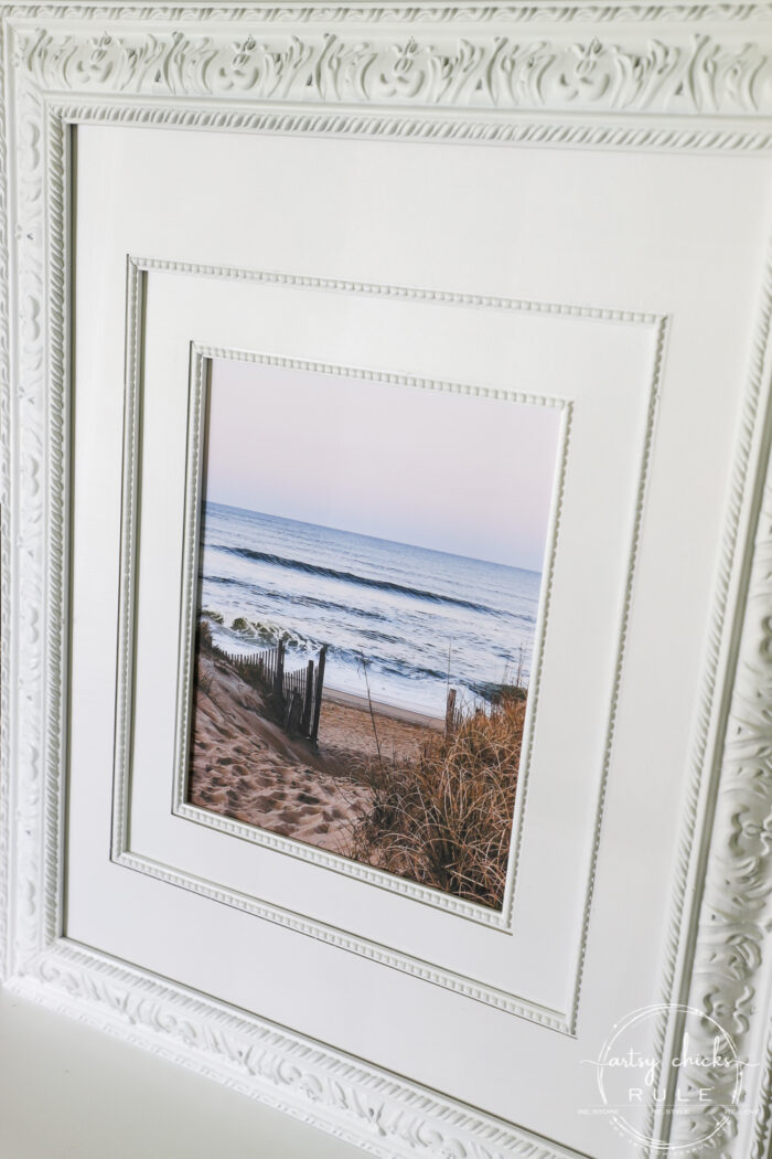 This beach scene wall art cost me SIX dollars! Yep! An old thrift store find, white spray paint and my own photo....budget friendly wall art! artsychicksrule.com #wallart #beachscenewallart #coastalwallart #diywallart #diybeachscene #framedbeachart