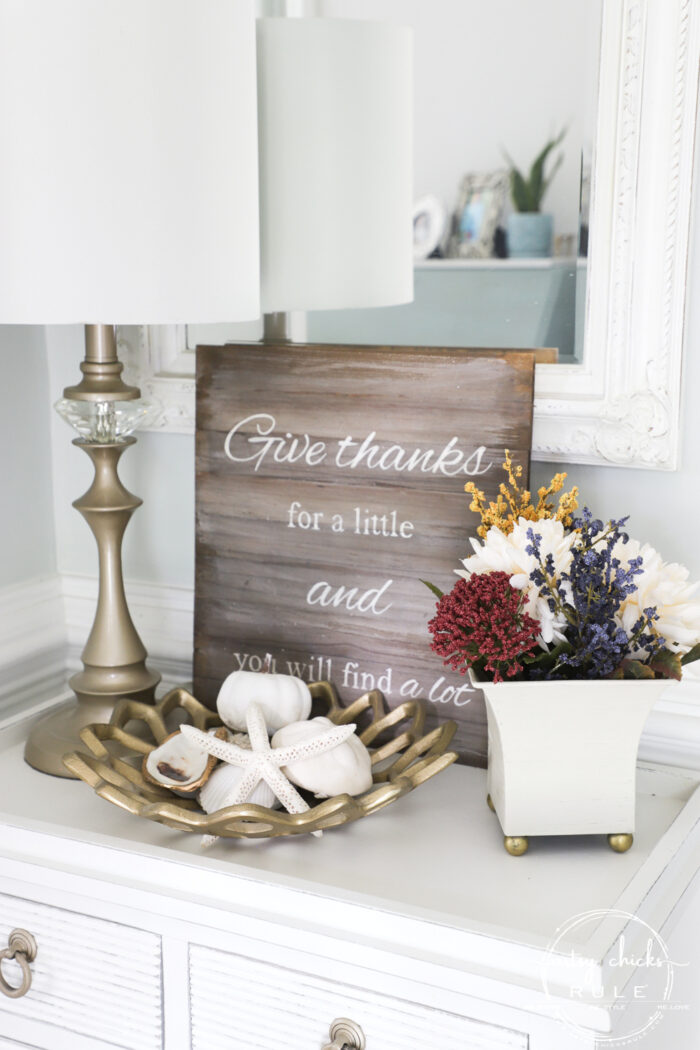 white foyer table with mirror and white dish with colorful fall floral