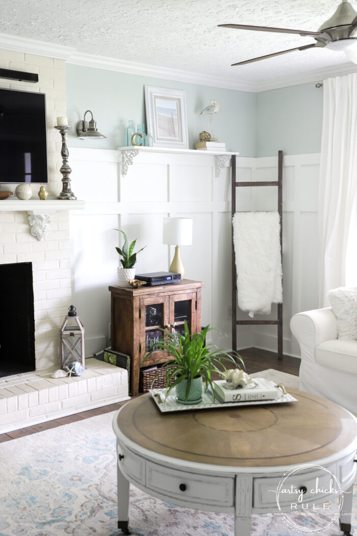 Coastal beachy style living room with round coffee table and thrifty decor