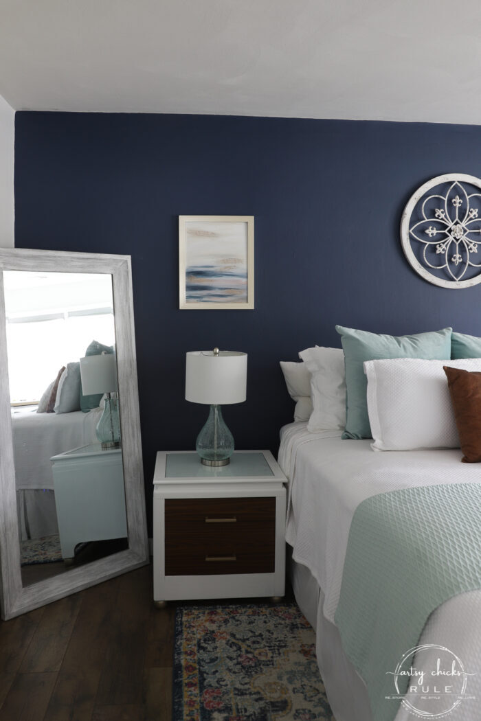 Abstract beach art on navy bedroom wall