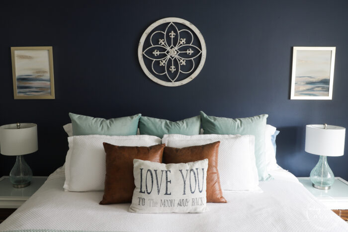 bed with pillows and matching abstract beach art on the walls
