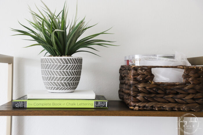 green potted faux plant on books with basket