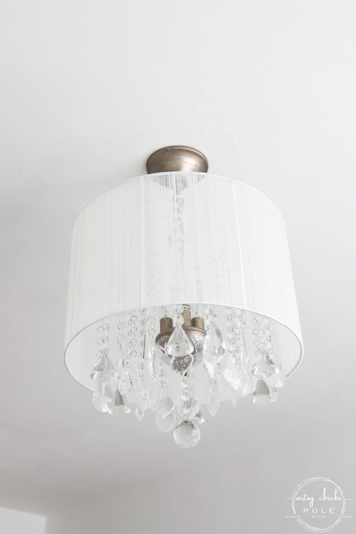 crystal chandelier and white drum shade