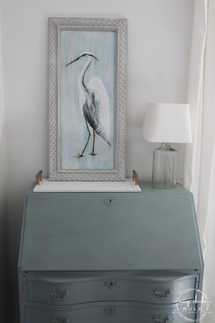 blue heron painting on blue desk with lamp