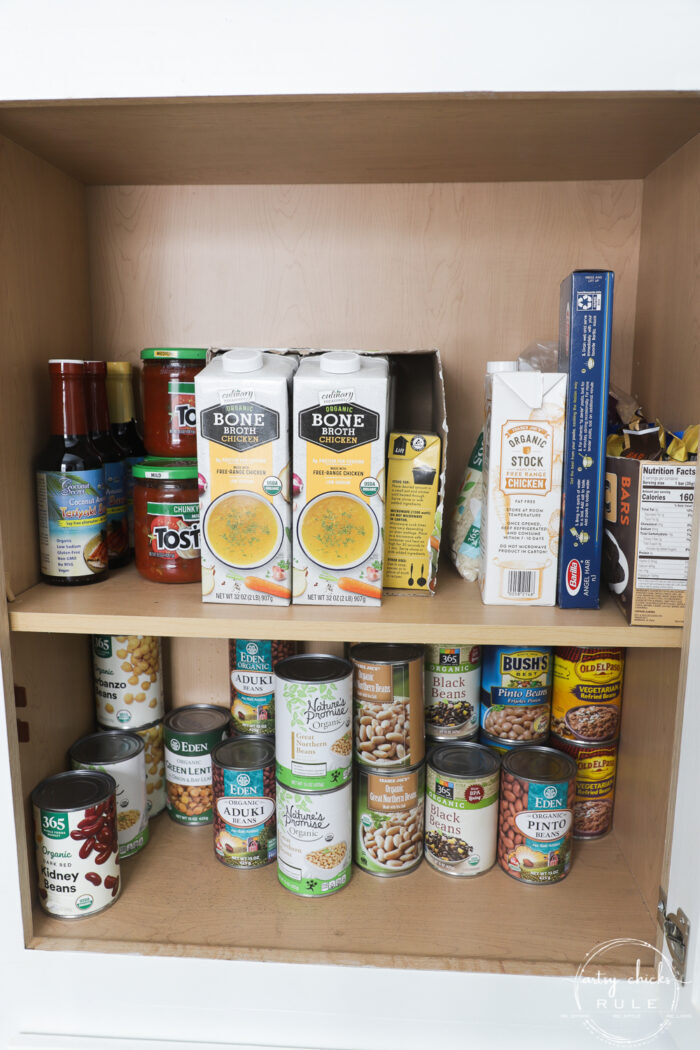 cabinet with cans of beans, chicken broth and salsa