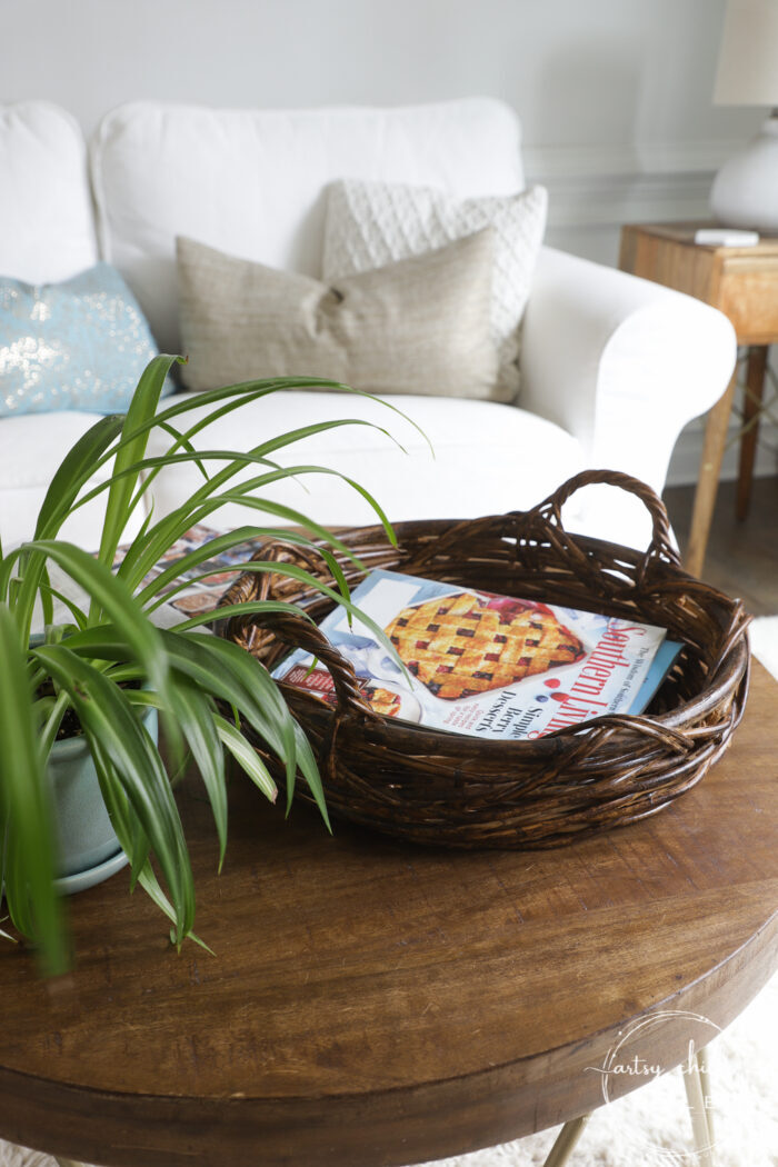 Dark stained round basket on small round coffee table with magazines