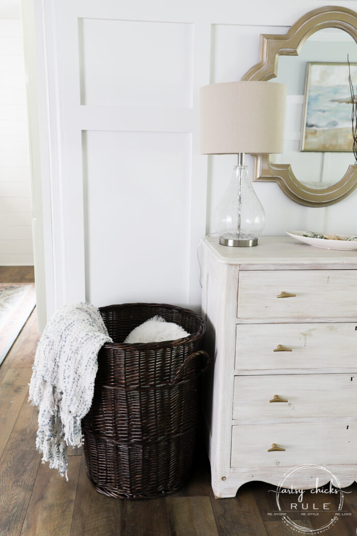 Dark brown tall basket filled with blankets and pillows