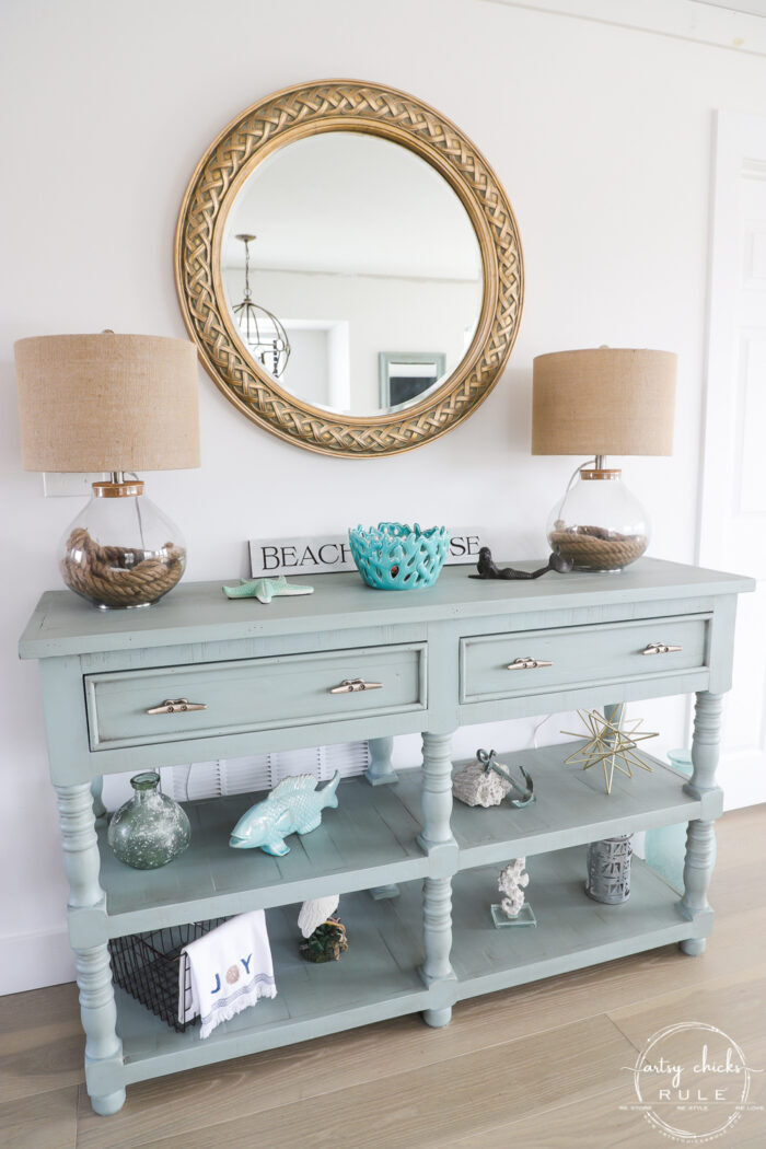 decorated aqua console with round gold mirror and two lamps