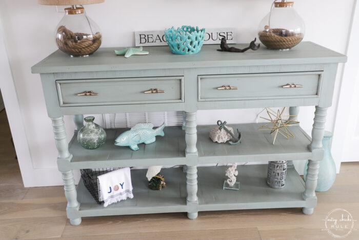 aqua console table decorated with coastal finds
