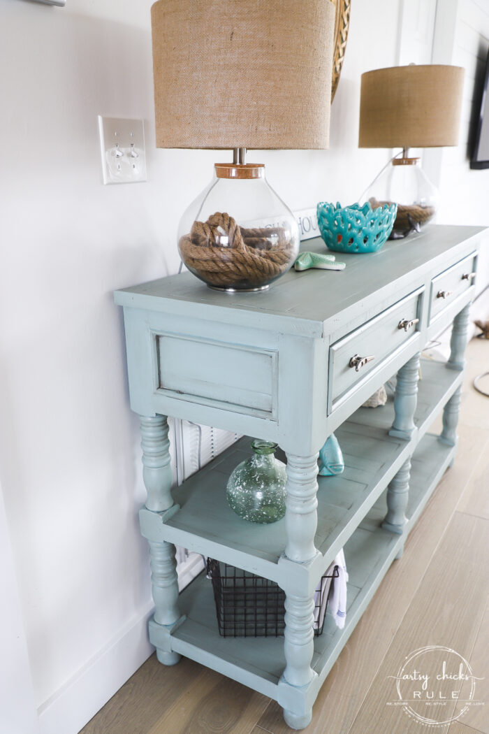 sideview of aqua console table with decor and lamps on wood floor
