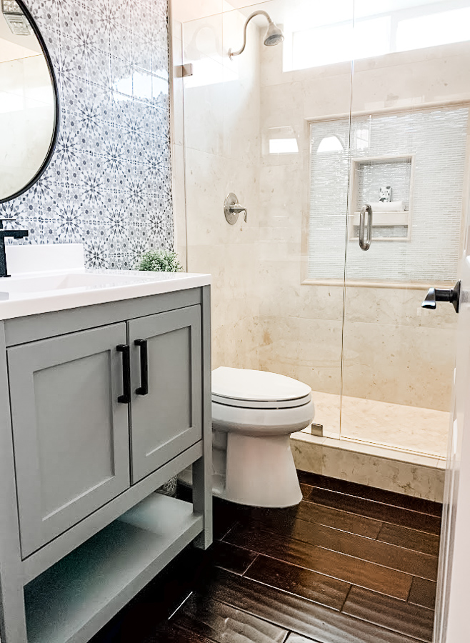 gray bath cabinet, wood floors and patterned decorative wall tiles