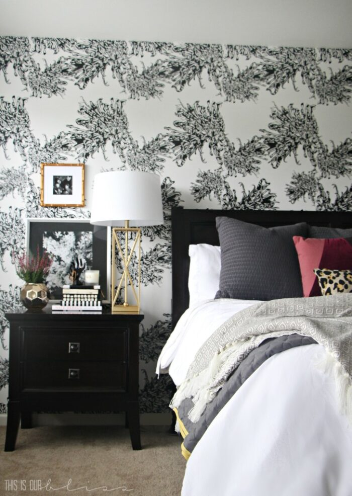 black and white wallpaper behind bed