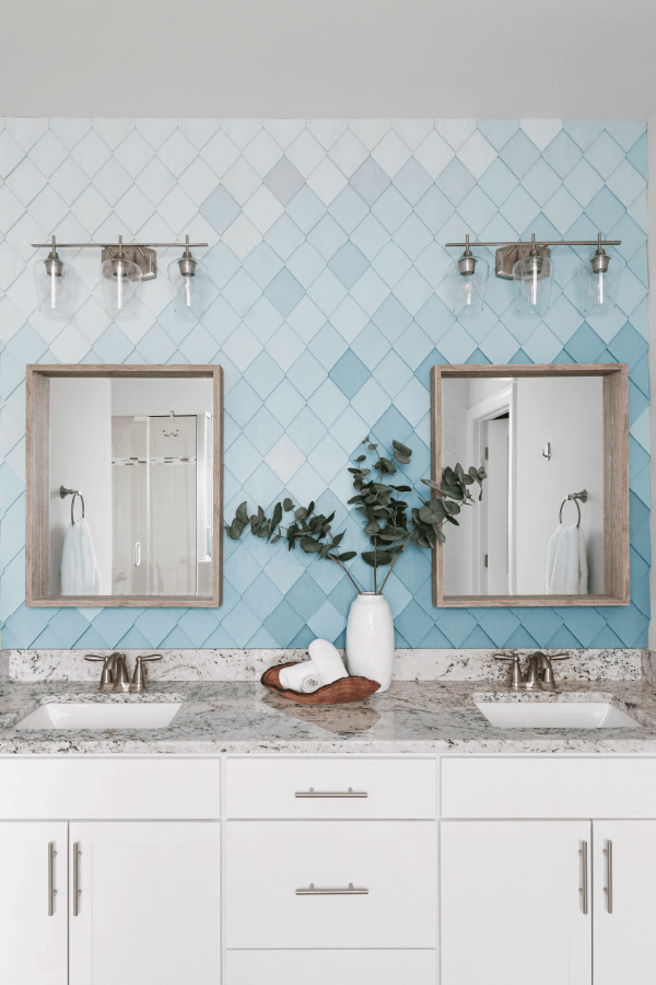 ombre blue wall with diamond shaped wood wall treatment behind 2 mirrors over sinks