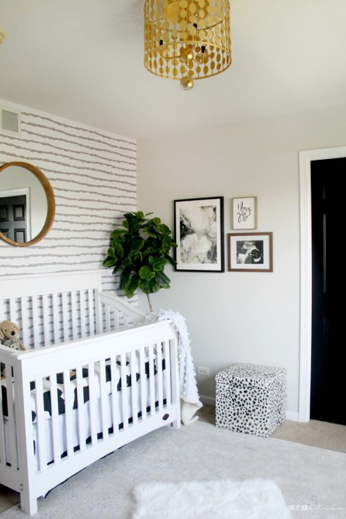 gray and white striped wallpaper accent wall with white crib
