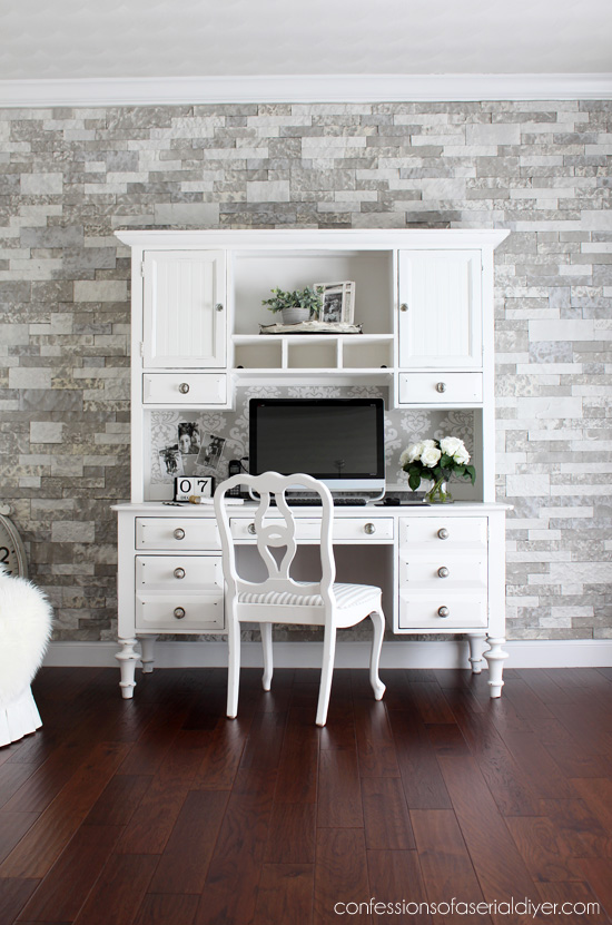 dark wood floor with white desk and chair and multi gray colored brick/stone wall