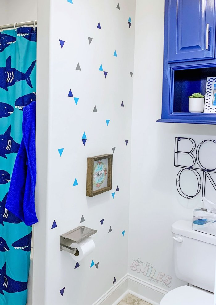 white wall with blue and gray triangle cutouts attached in bathroom