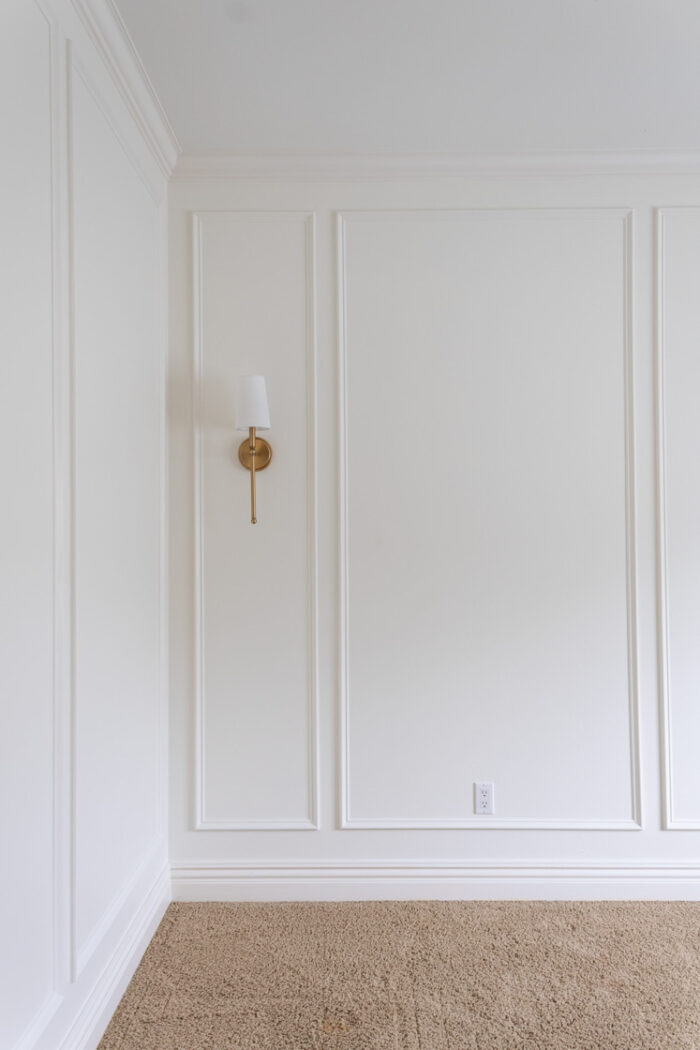 white wall with simple wainscoting and gold lamp