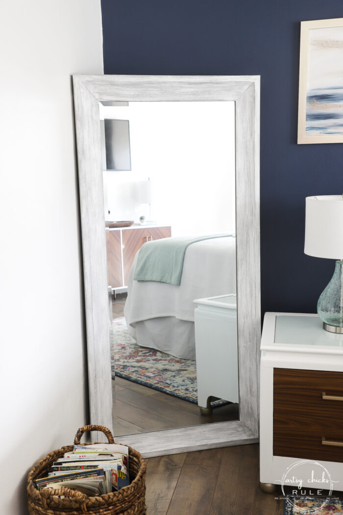 navy wall with floor mirror painted white