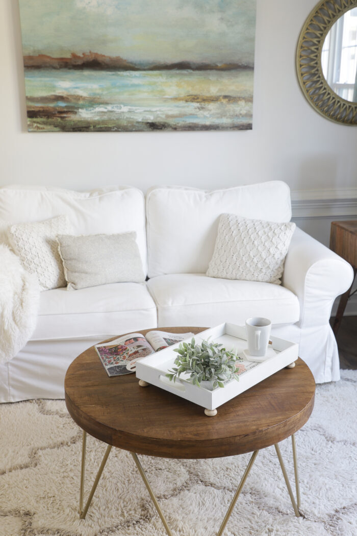 white couch, white tray, wood coffee table