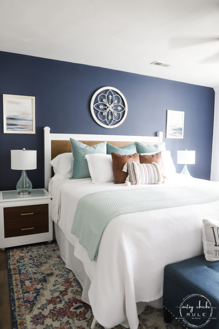 finished full shot of bedroom with white bed, colorful rug, white and woo headboard