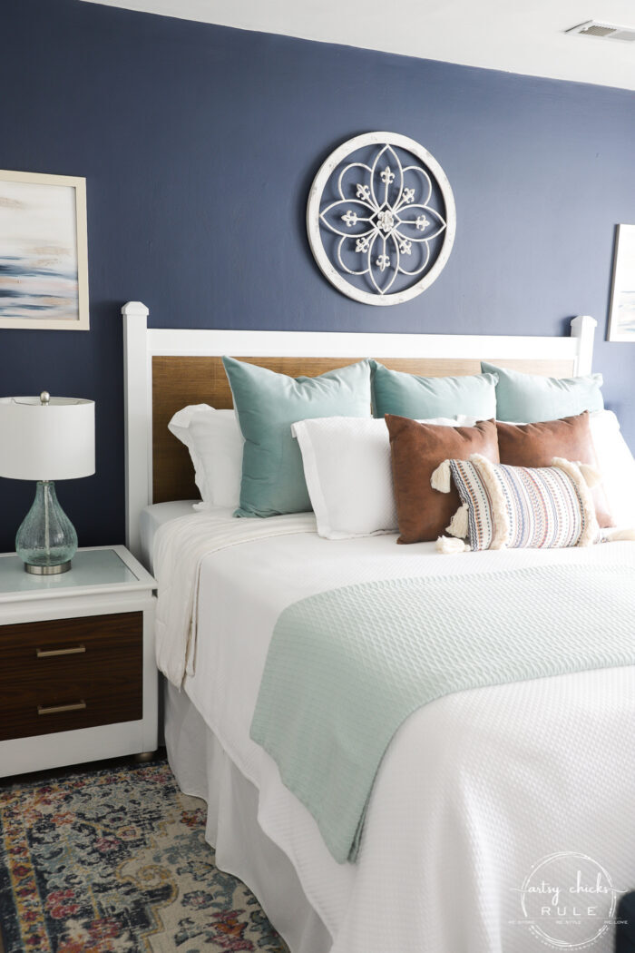 Navy wall, bed with pillows, colorful rug
