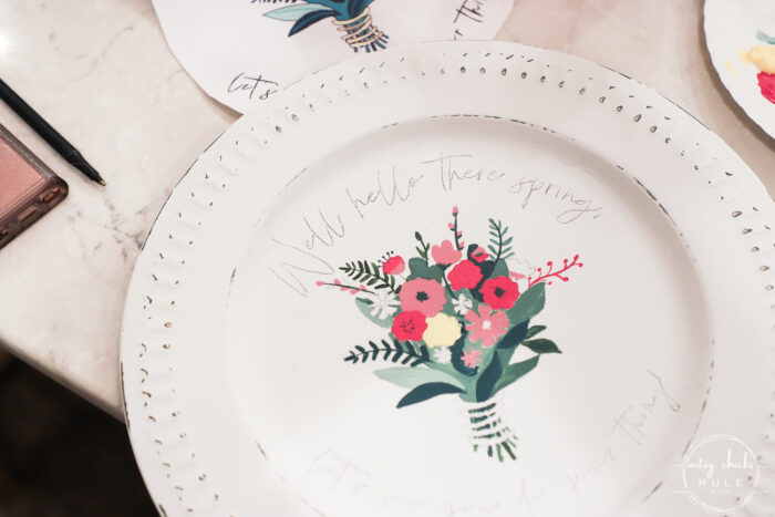 white charger plate with pink flowers, green leaves and a yellow flower