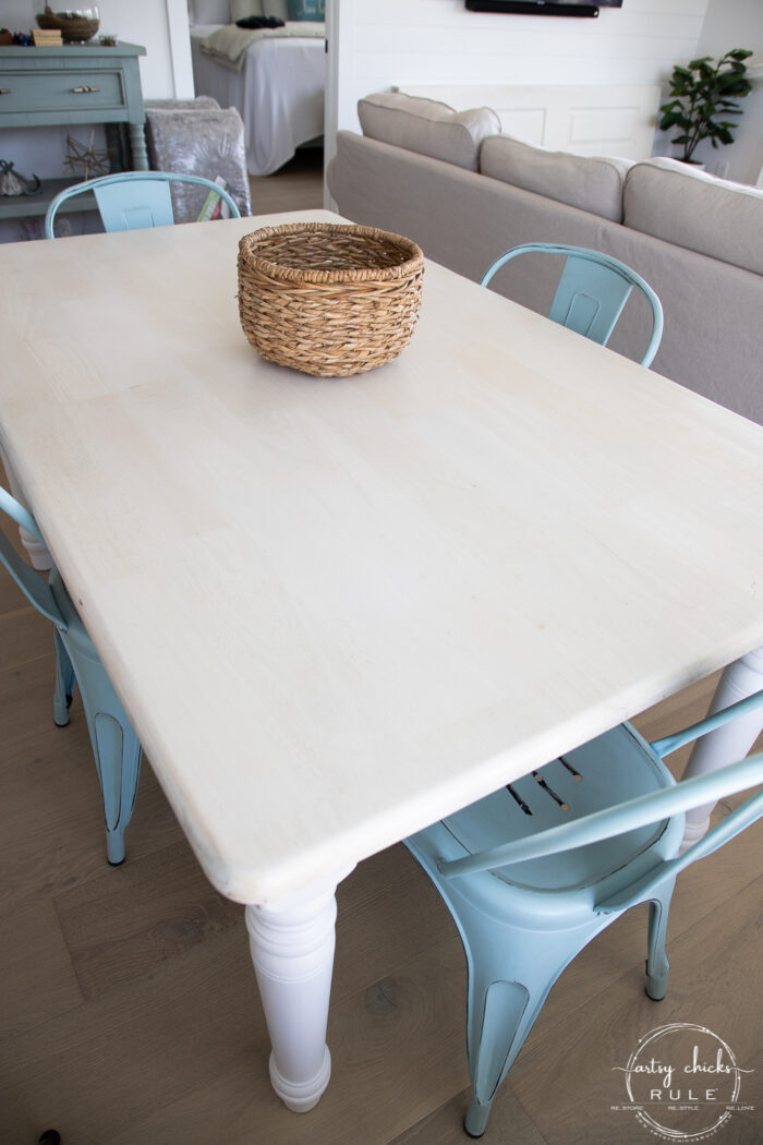 bleached tabletop with basket and blue chairs
