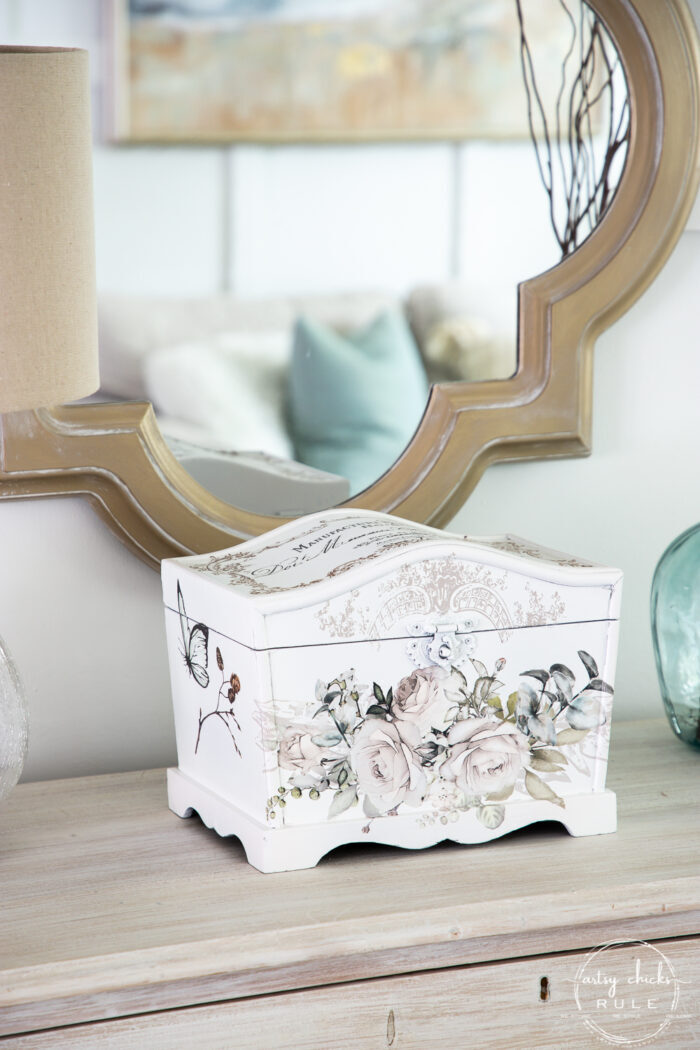 white treasures box with rose floral pattern on front with gold mirror behind