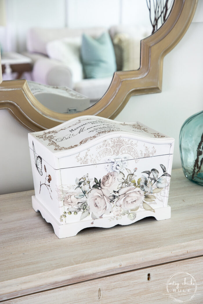 whitewashed dresser with white keepsake box and gold mirror