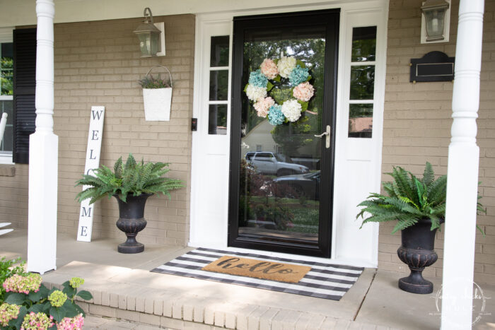 front door with white columns and black and white plaid mat