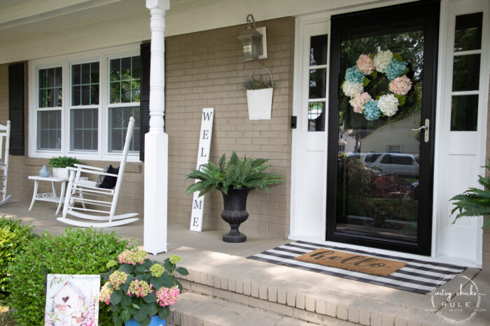 black and white front porch with white rockers and welcome sign