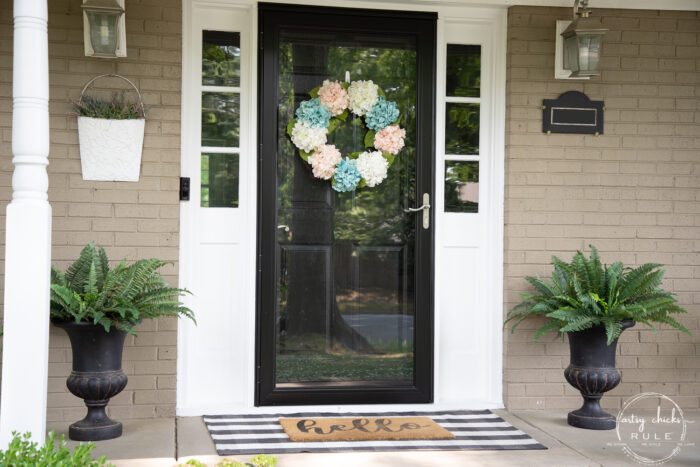 black front door with wreath and green ferns on each side