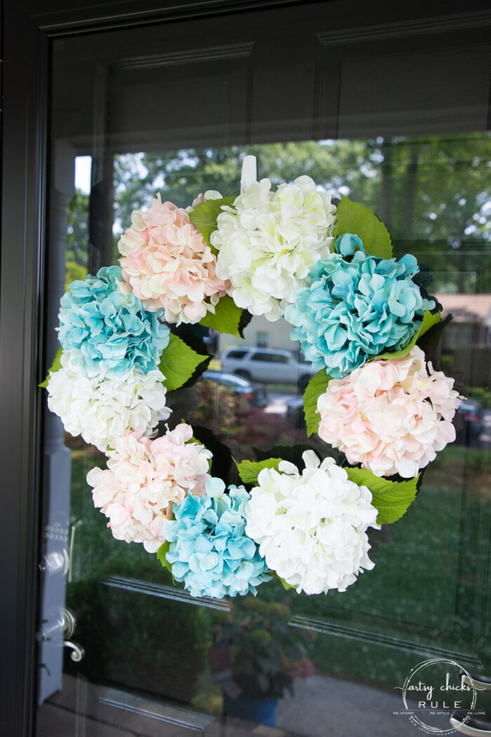 pink, white and teal hydrangea wreath on glass door