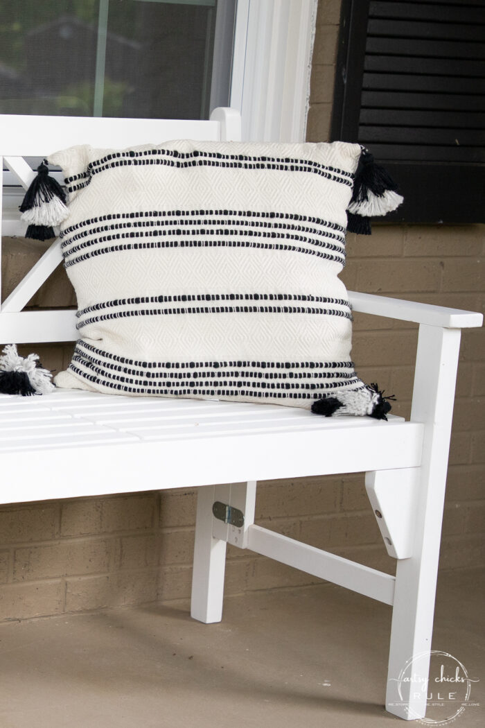 close up of black and white pillow with tassles