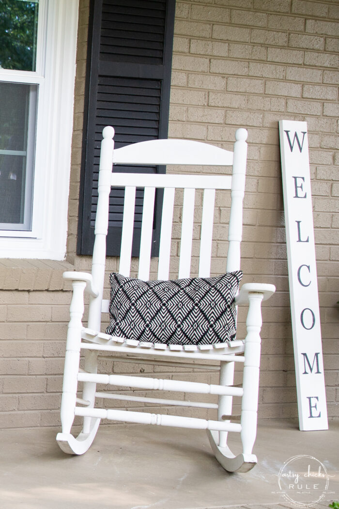 white rocker with black and white pillow and welcome sign