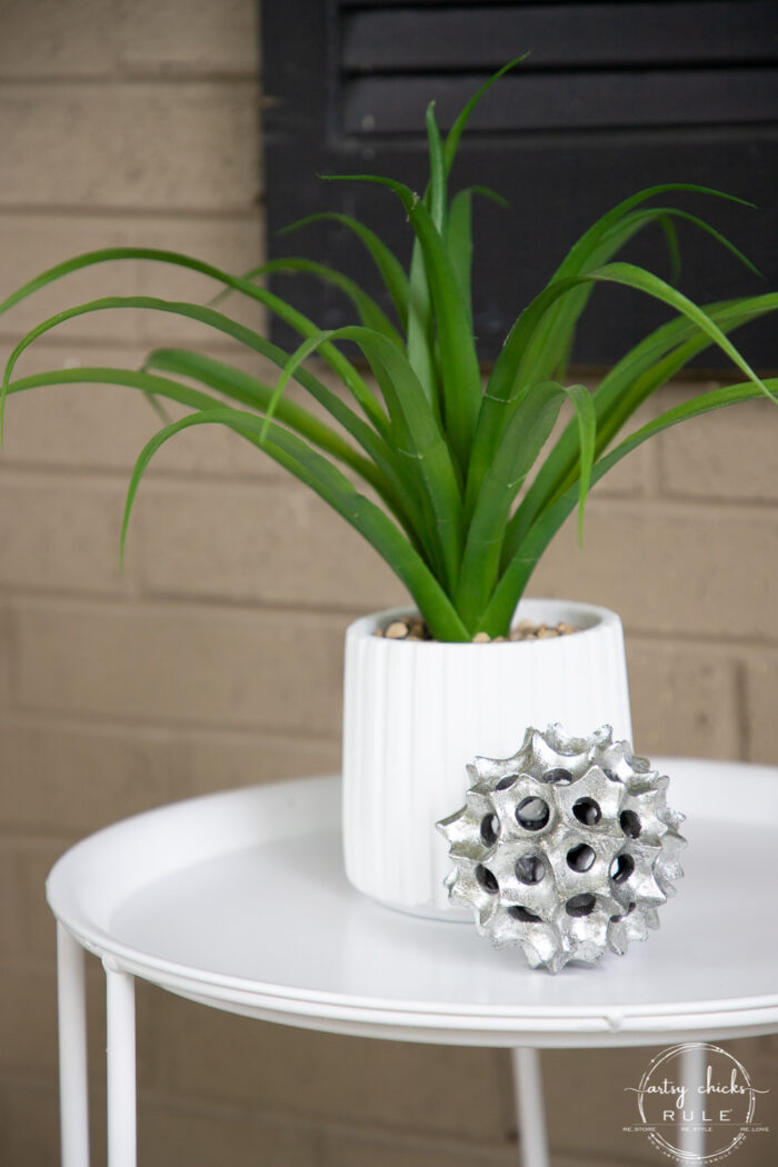 white jar, green plant and silver ball