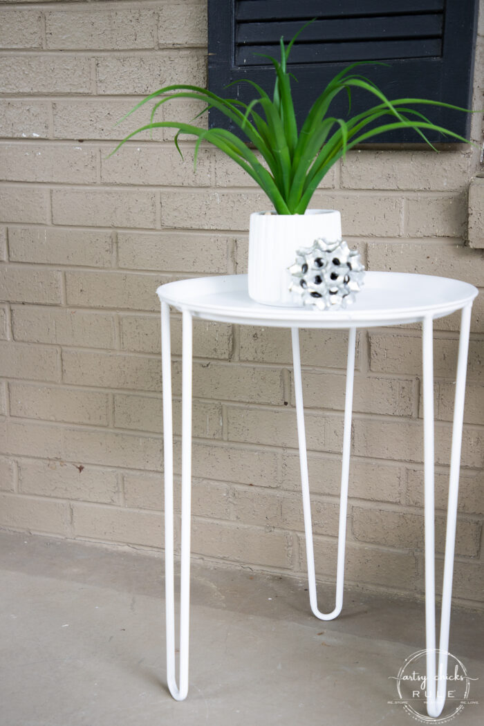 white metal table with green plant and silver decor