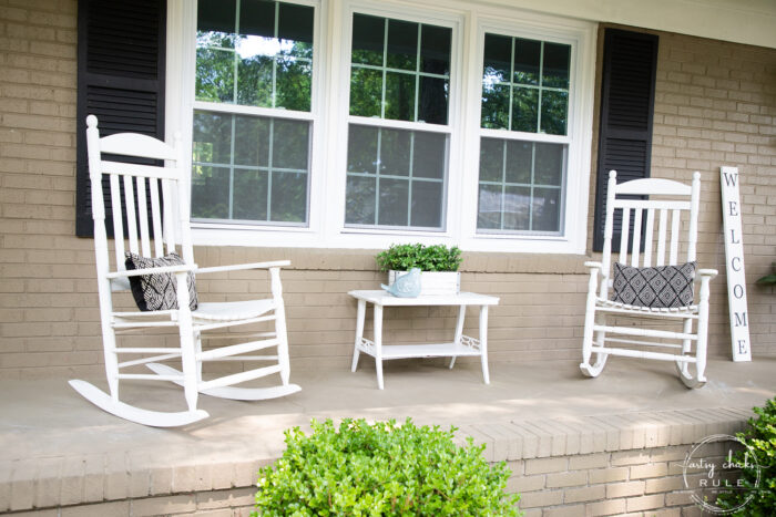 2 white rockers with white table tan house black shutters