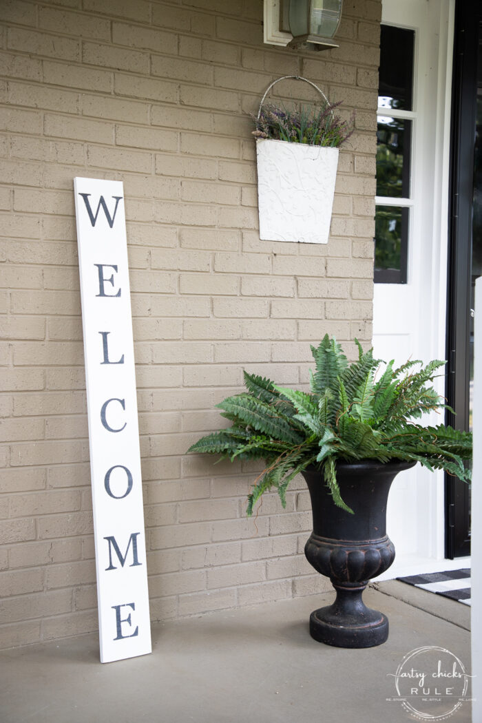 tall welcome sign with green fern
