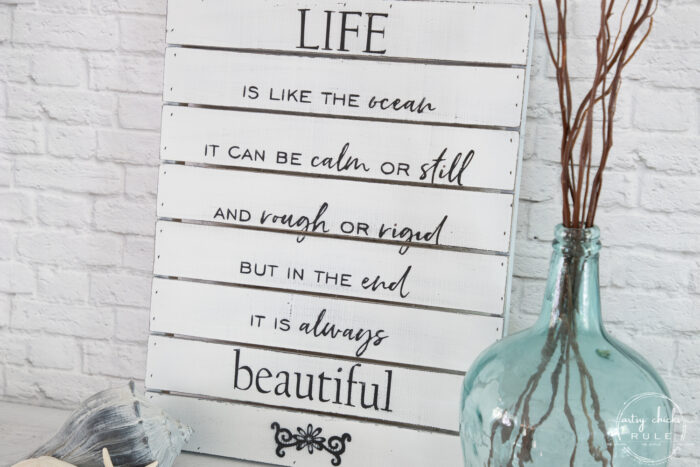 life is like the ocean sign with aqua glass jar and branches with seashells