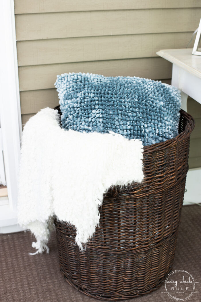 dark brown tall stained basket with white throw and blue pillow