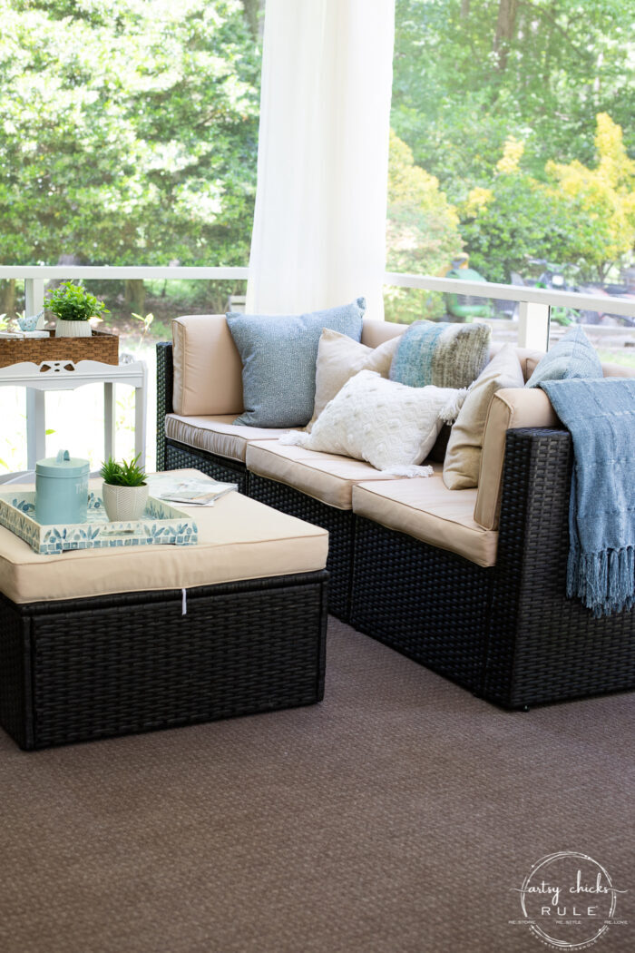 dark brown wicker patio furniture with aqua and tan pillows