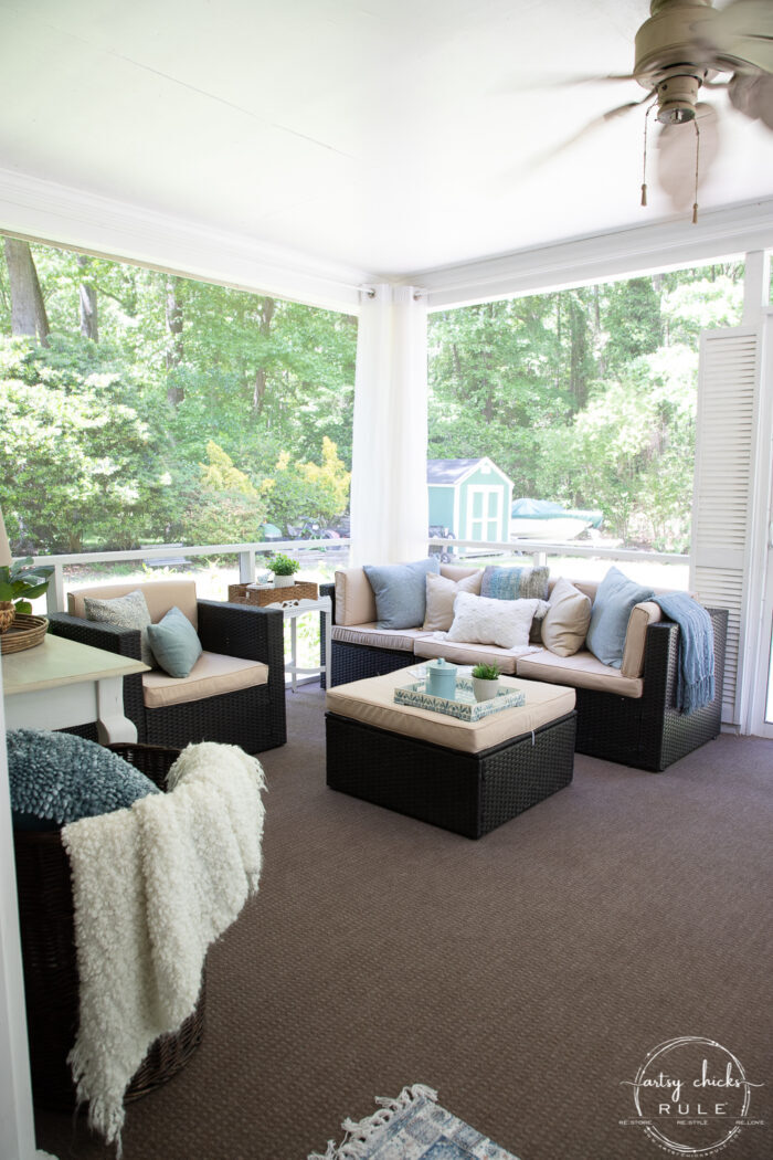 aqua and brown porch with tan pillows and brown carpet