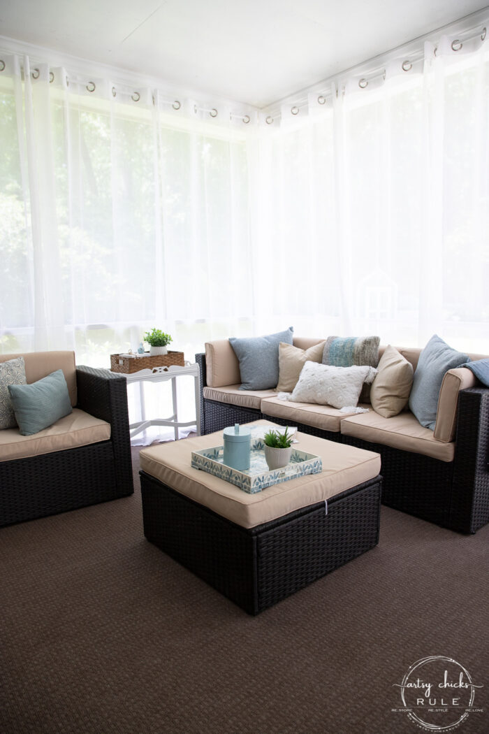 patio furniture with sheer white curtains behind
