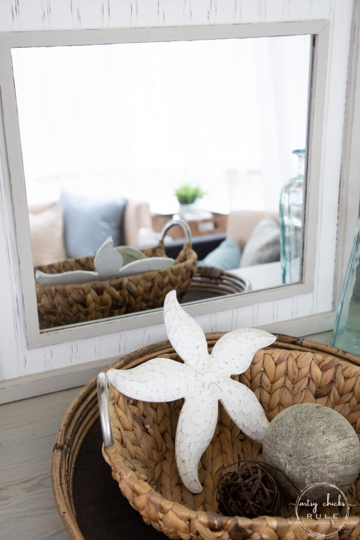 basket tray with basket and white starfish in front of mirror